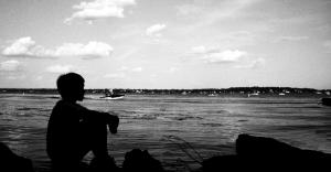 mujer sentada cerca del mar con el horizonte al fondo