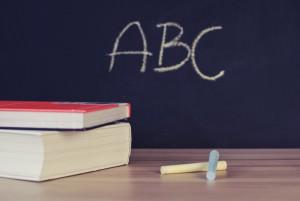 Una pizarra con ABC escrito y unos libros en primer plano